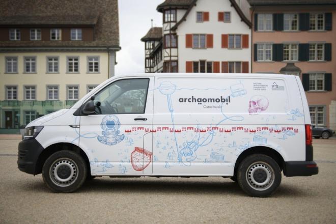 Bild: Jonas Hänggi/Verein Archäologie Mobil; Das Archäomobil Ostschweiz hat zwei verschiedene Seiten. Diese präsentiert das UNESCO-Welterbe der Pfahlbauten.